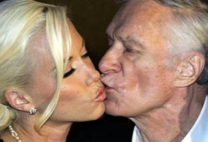 An older man is kissing a young woman